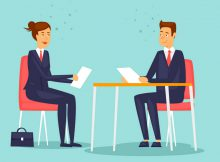 Small business owner sits down with her new employee as part of first day onboarding